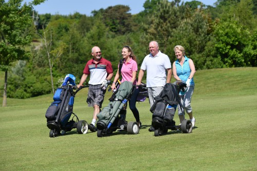 Two men and two women wheeling three golf bags on golf course